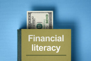 Image of a book with financial literacy on the cover and a $100 bill coming out the top