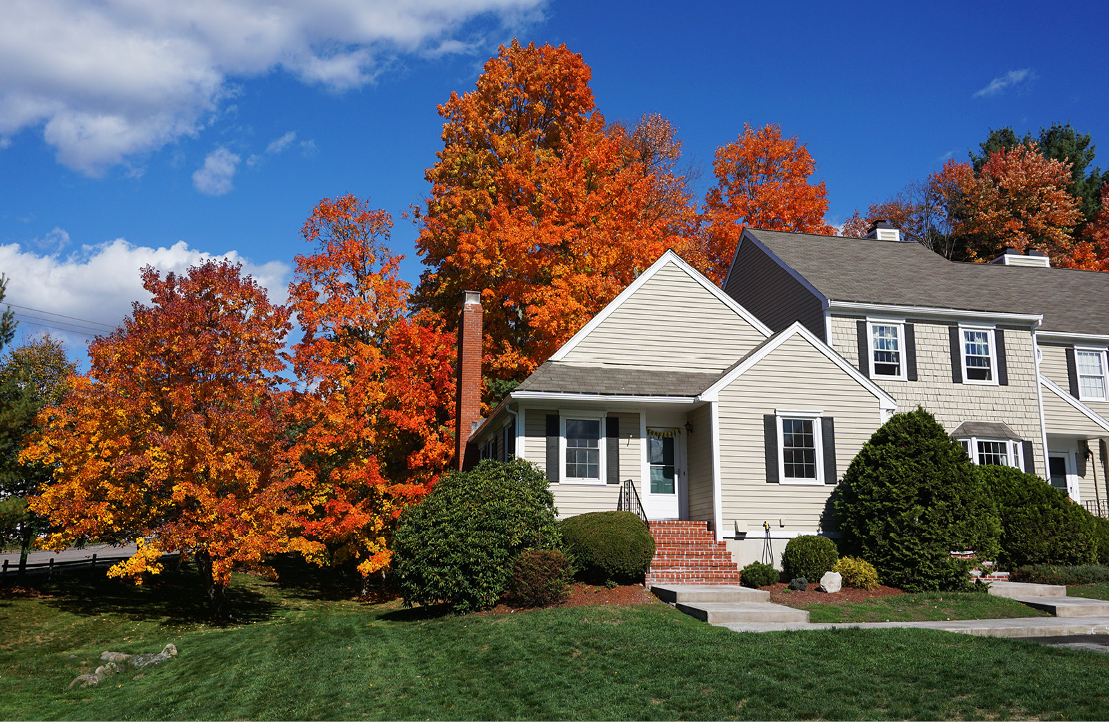 Image of a house/condo in the fall with foliage.