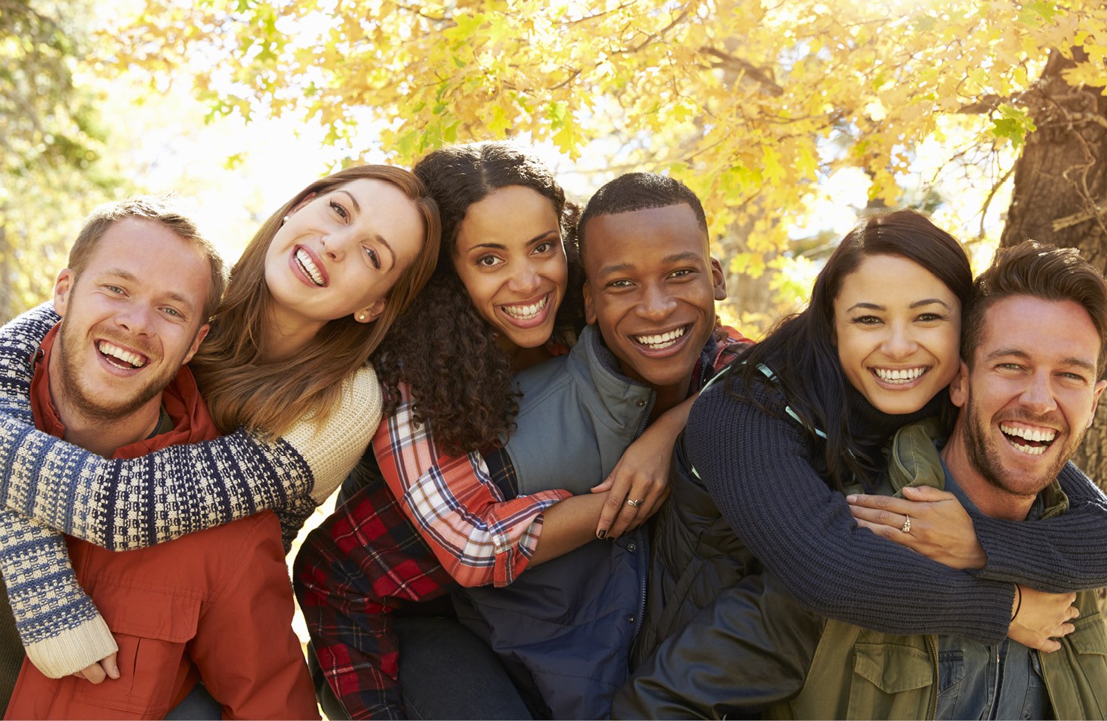 Image of a group of people both male and female together smiling with a fall themed background.