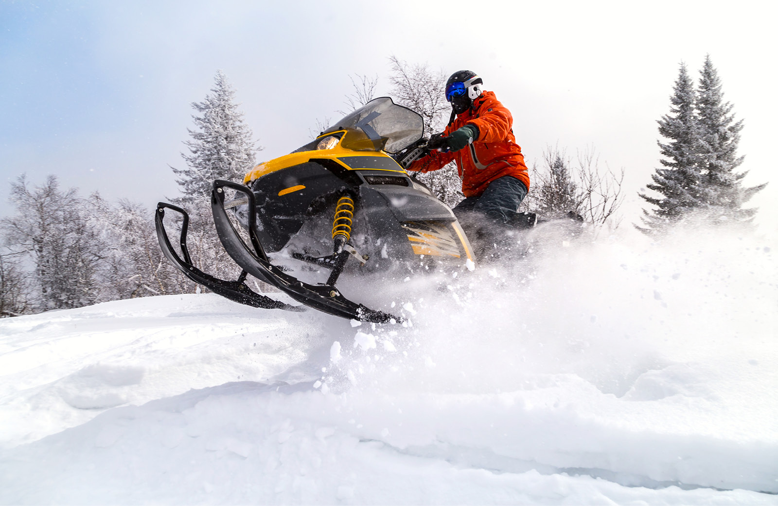 Image of a rider on a yellow snowmobile on snow in the winter.